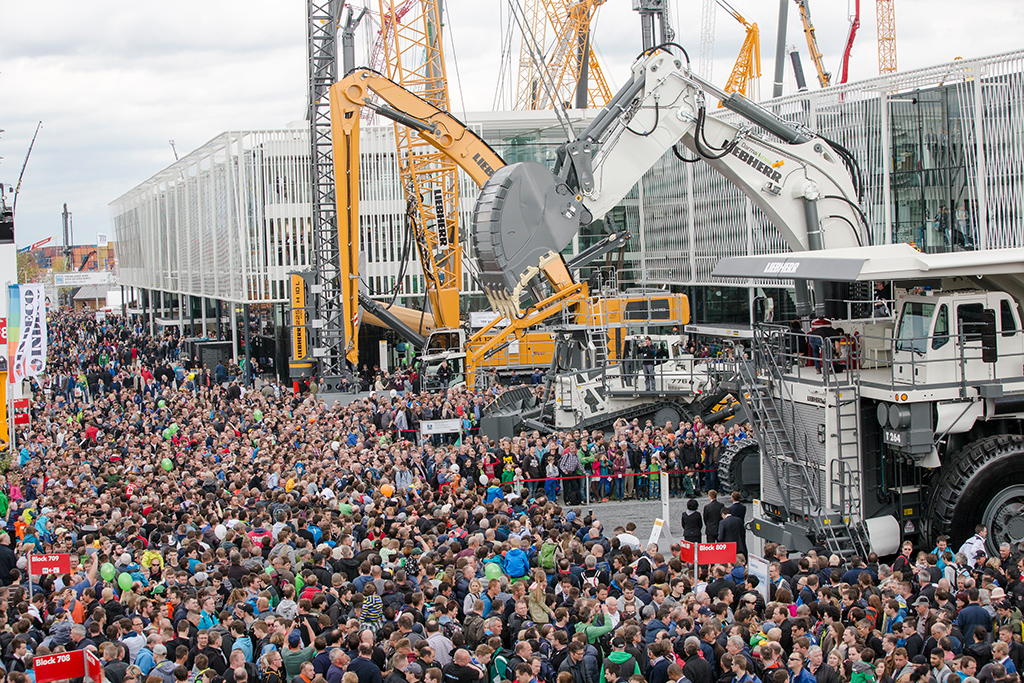 Visitors during a demonstration at the Liebherr booth